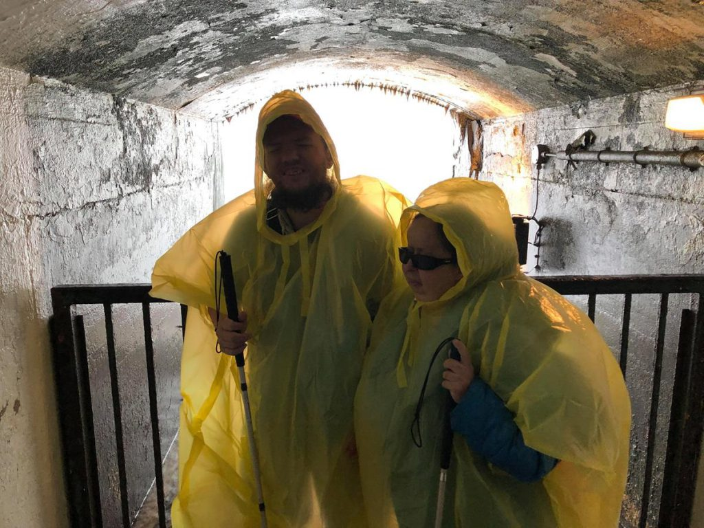Tony and Tatiana inside a concrete opening behind the curtain of the falls. Wearing waterproofs to protect themselves from the spray.