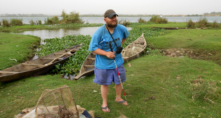Tony on the grassy bank of the wide Niger River in Bamako, Mali. Canoes and fishing nets around him. March 2012.