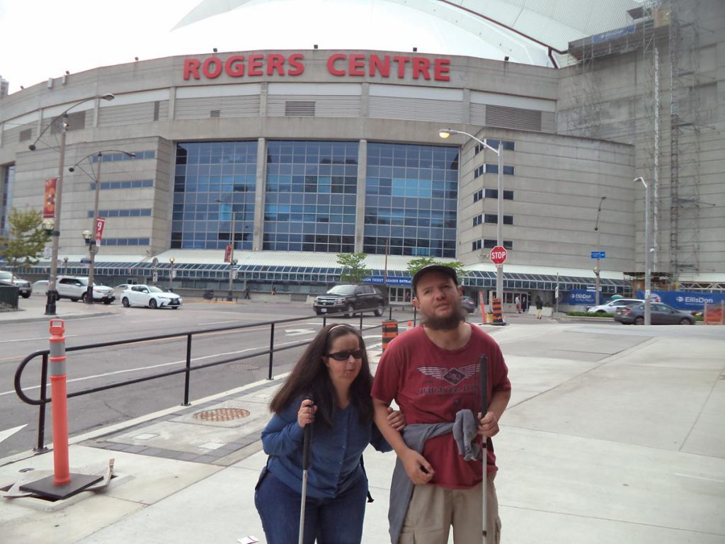 Tony and Tatiana in front of the Rogers Centre, formerly the Sky Dome. This multi-purpose stadium is located close to the CN Tower. It is home to the Toronto Blue Jays, the city's famous professional baseball team. It is also used for conventions and music concerts.