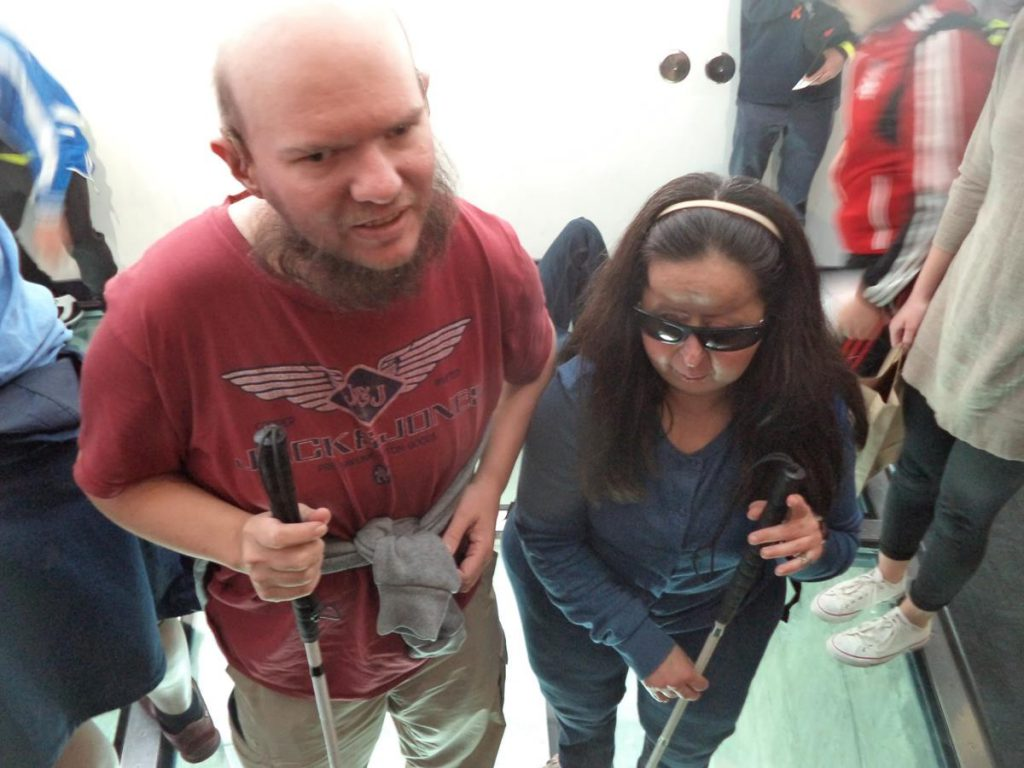 Tony and Tatiana standing on a glass floor inside one of the CN Tower's observation decks.