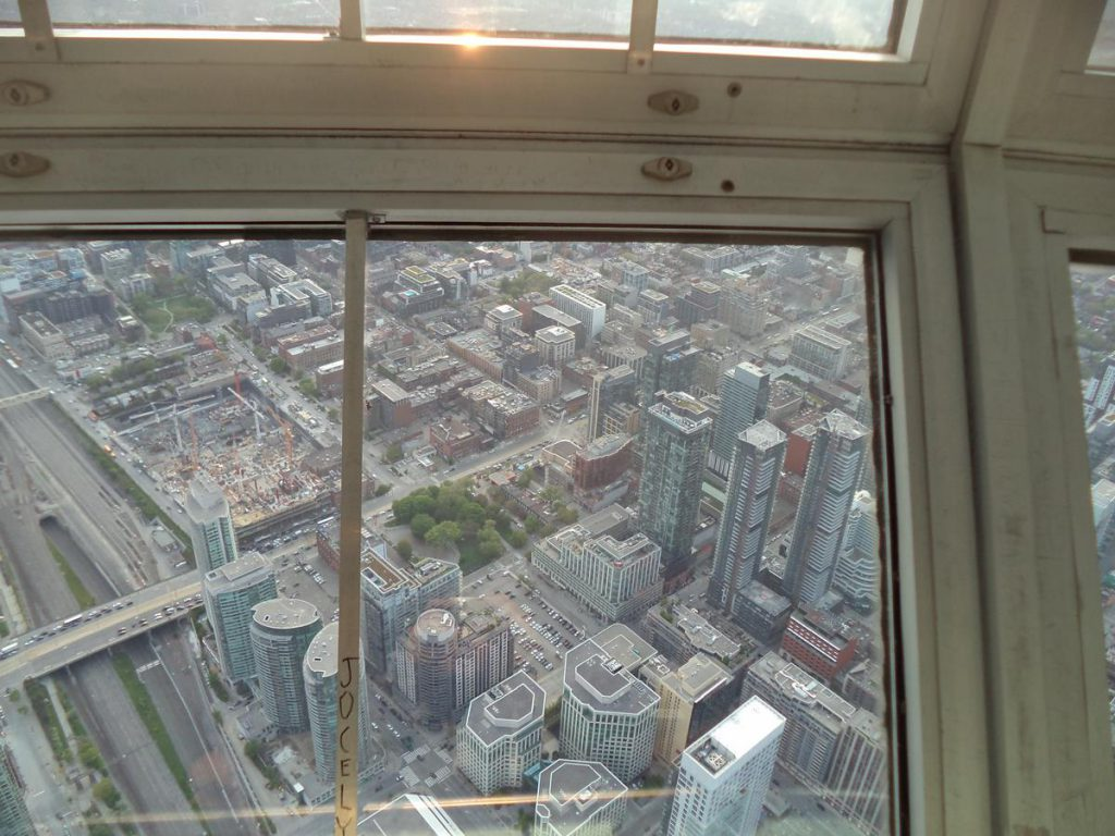 Looking down from a window inside the CN Tower with buildings and streets of the city spread out below.