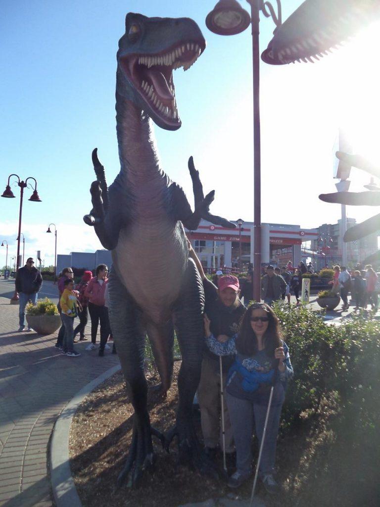 Tony and Tatiana next to a dinosaur model. It is similar to a Tyrannosaurus rex but smaller.
