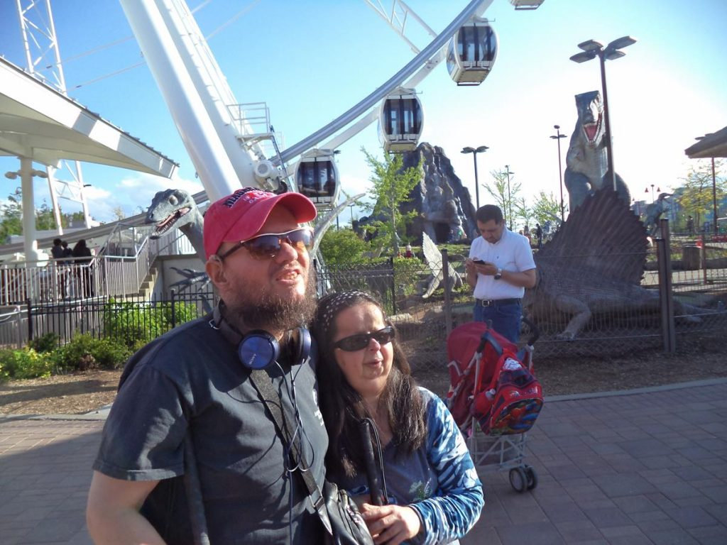 Tatiana and Tony with the Niagara SkyWheel and more dinosaur models in the background. The Niagara SkyWheel is a 53 metre (175 foot) tall Ferris wheel.