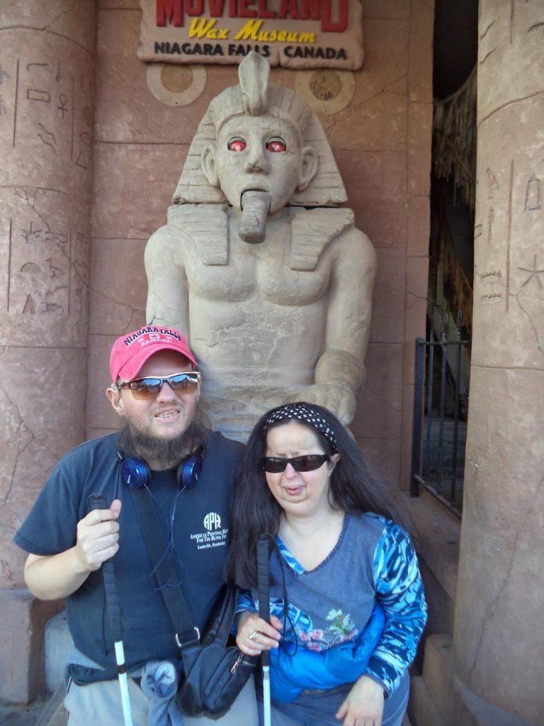 Tony and Tatiana in front of a model of an Egypt pharaoh statue.