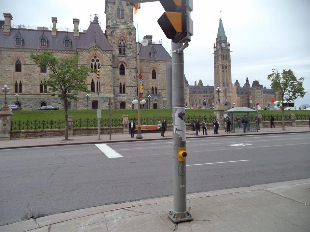 The Canadian Parliament Buildings located on Parliament Hill. In the foreground is the West Block, which contains offices, and further away to the right, the Centre Block, which houses the Senate and Commons chambers. The Peace Tower stands in the middle of the Centre Block's front facade. It is a clock and bell tower which is 98 metres (322 feet) in height. The buildings are Gothic Revival in style and were constructed from 1859, although the Centre Block was destroyed by fire in 1916 and subsequently rebuilt in a similar style to the original design.