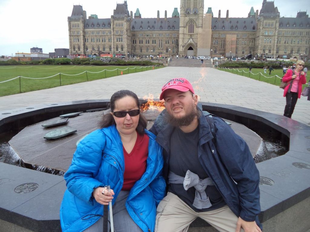 Tony and Tatiana sitting in front of the Centennial Flame on Parliament Hill. It was constructed to commemorate Canada's 100th anniversary as a Confederation in 1967. It is 12-sided with a flame fuelled by natural gas in the centre. Around the flame is a fountain, with water flowing down a ledge to a channel on the outside. The ledge contains the shields of Canada's 13 provinces and territories (Nunavut was added in 2017 following its creation as a territory in 1999).
