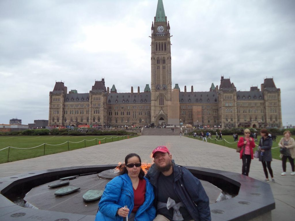 Tatiana and Tony sitting on the Centennial Flame with the Centre Block of the Parliament Buildings and the Peace Tower visible in the background.
