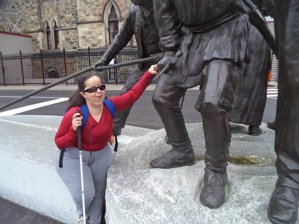 Tatiana touching a First Nations warrior depicted as part of the War of 1812 Monument. A Royal Navy sailor pulling a rope can also be seen.