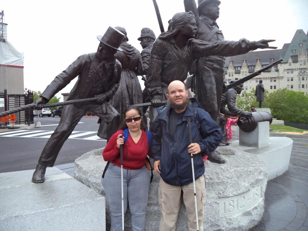 Tatiana and Tony in front of the War of 1812 Monument. Other figures depicted include a member of the Royal Newfoundland Regiment firing a musket and a woman bandaging the arm of a Quebec soldier of the Canadian Voltigeurs.