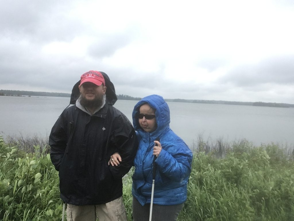 Tony, Tatiana standing by Lake Astotin in Elk Island National Park. Long grass in the foreground with the lake beyond. Astotin is the largest lake in the park, located near the main visitor centre.