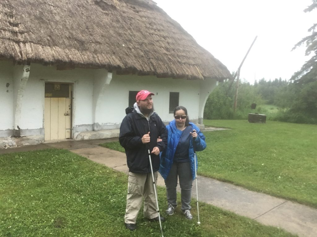 Tony and Tatiana in front of the Ukrainian Pioneer Home: a white painted building with a thatched roof. Located up a slight hill in Elk Island National Park. It's been a Classified Federal Heritage Building since 1993 and is located at Astotin Lake Recreational Area. It was constructed in 1951 and is an excellent and attractive example of the traditional form and plan of a Ukrainian-Canadian homestead.