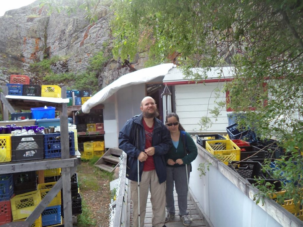 Tony and Tatiana outside the Old Town Glassworks. Lots of plastic crates containing glass bottles can be seen.