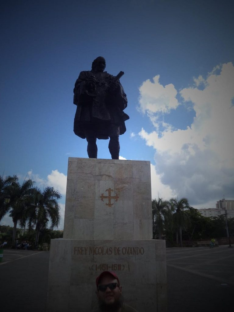 Tony in front of a bronze statue of Frey Nicolas de Ovando, standing on a stone base, located in Plaza España. Nicolas de Ovando (1460 – 1511) was a Spanish soldier from a noble family who arrived in Santo Domingo in 1502 and became Governor of the Indies (Hispaniola) until 1509. His administration brutally exploited and enslaved the island's indigenous peoples.