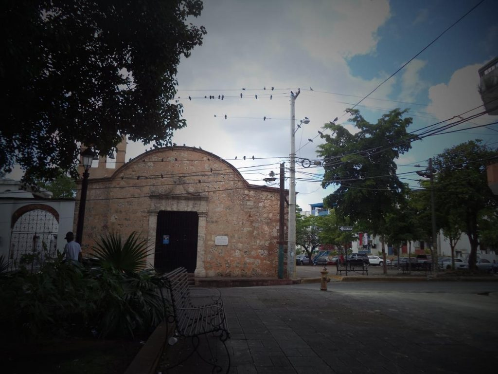 Looking across a square to the small church of San Miguel (Iglesia San Miguel). This old church has a rectangular main doorway with a gently curving roof above. There is a small bell tower on the left side.