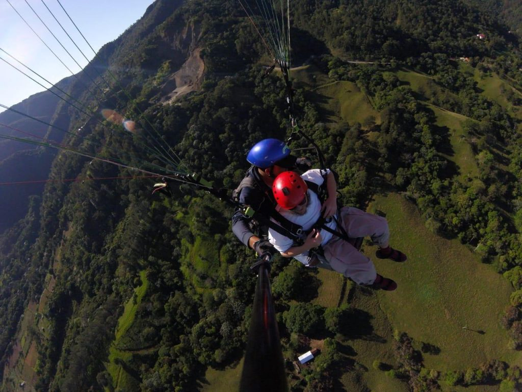 Tony attached to a harness with an instructor while paragliding high above the ground. Excellent view of the surrounding landscape: a mixture of small fields and forested areas.