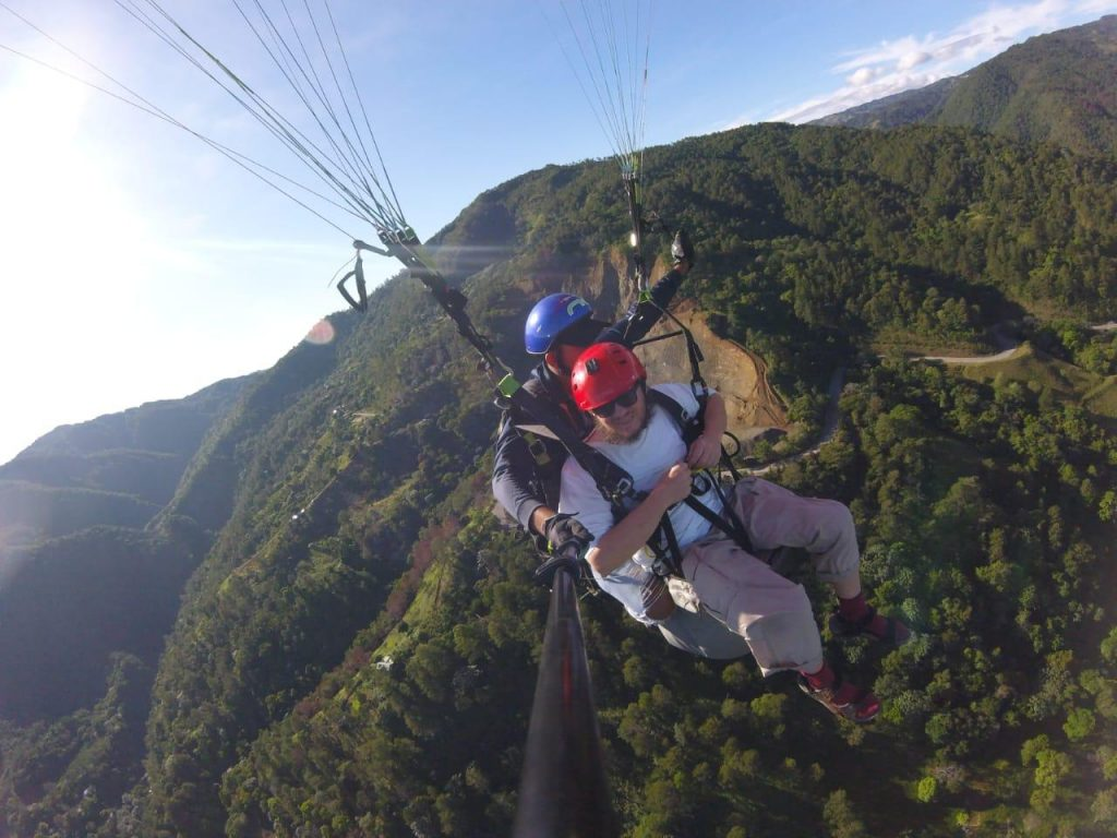 Tony paragliding. A semi-wooded hill in the background.