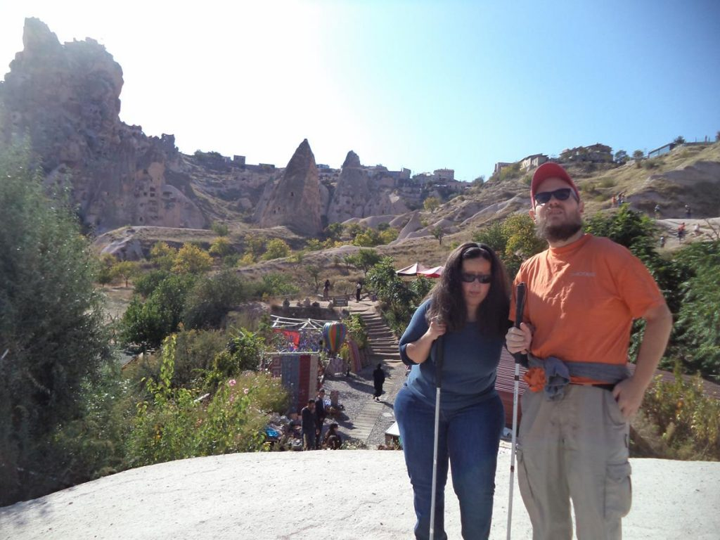 Tatiana and Tony in the distinctive rocky landscape at Göreme. A cliff in the background with caves cut into the soft rock, as well as modern buildings above. Souvenir stalls and a café below.