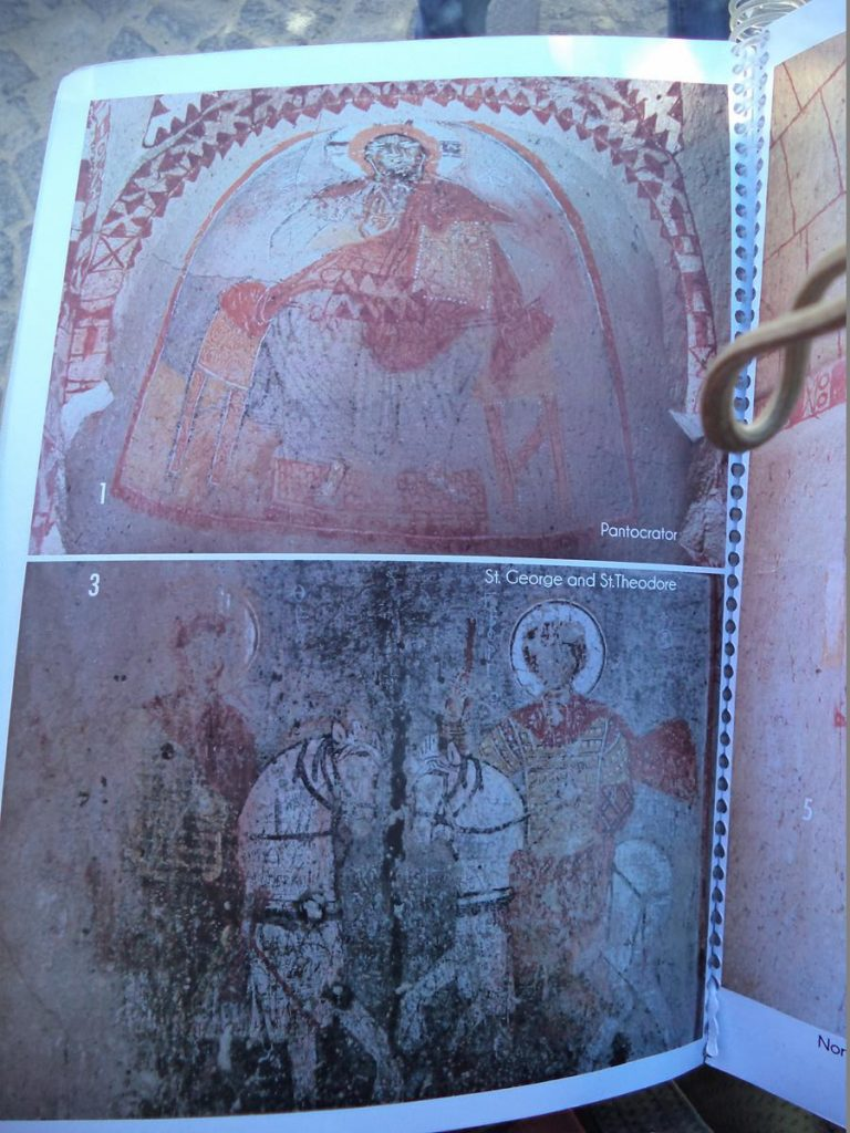 Two frescos inside St Barbara church photographed inside a book, because no photography is allowed inside the church itself. One fresco shows St George and St Theodore on horse back, while the other depicts Christ Pantocrator, a full body representation of Jesus Christ as ruler of all things.
