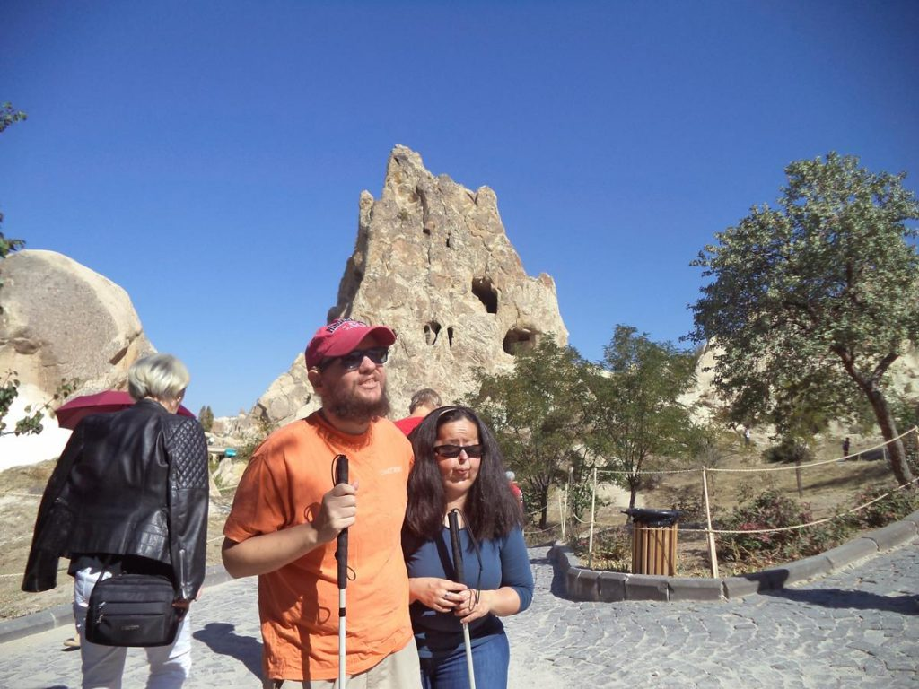 Tony and Tatiana at Göreme Open-Air Museum. In the background a pinnacle of rock with caves cut into it: a common sight around Göreme.
