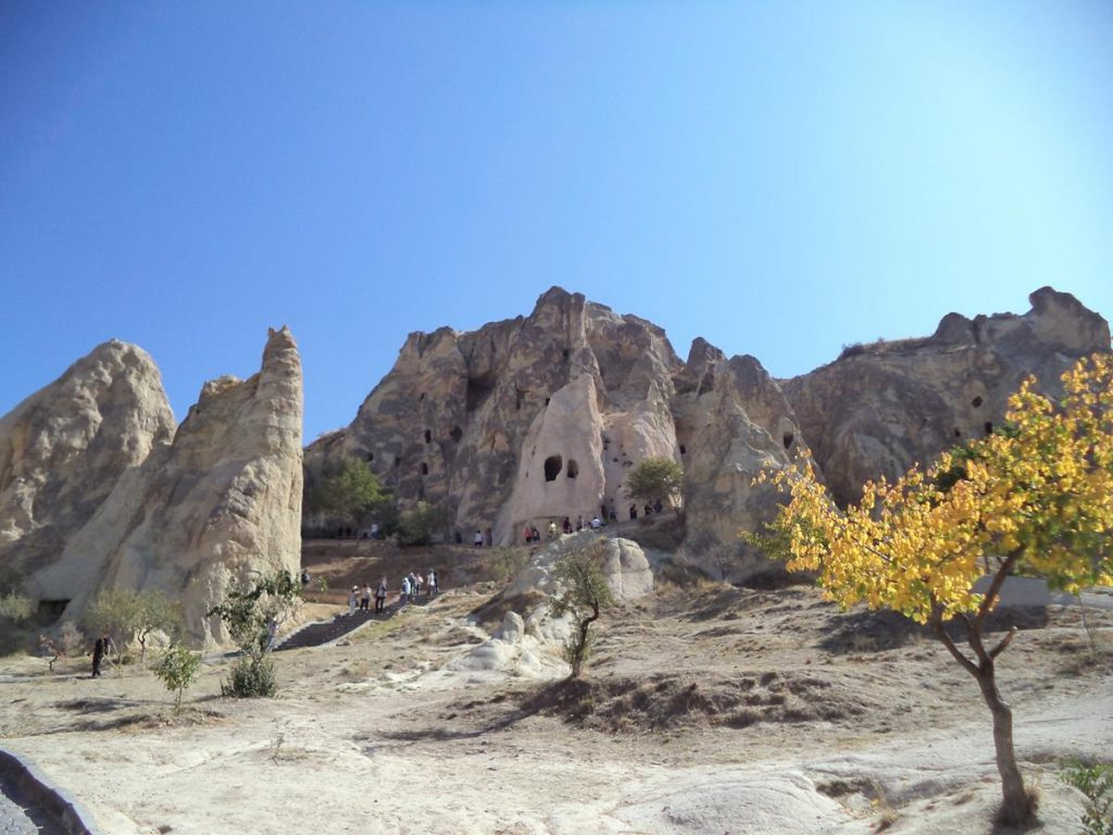View across part of the Göreme Open-Air Museum site. The foreground slopes upwards covered with parched patches of grass and occasional small bushes and trees to a towering outcrop of rock with various doors and windows visible cut into it.