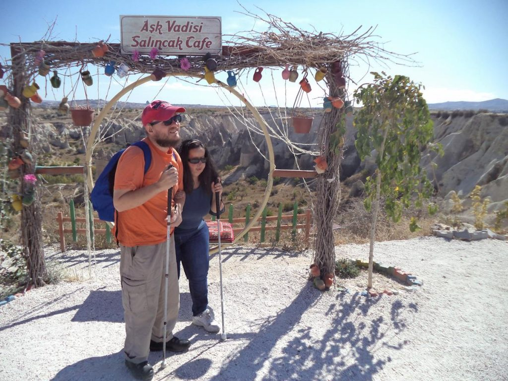 Tony and Tatiana at a view point looking over Love Valley. In the foreground, a seat under an arch, decorated with pottery jugs. A sign for Aşk Vadisi Salıncak Café above.