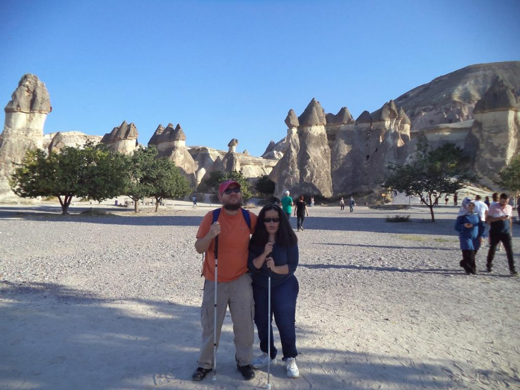 Tatiana and Tony at Urgup (Ürgüp). Groups of fairy chimneys can be seen in the background. These towering conical formations, often noted for their phallic appearance, are commonly seen in the Cappadocia region. They have formed due to their protective cap of erosion-resistant basalt rock, which has allowed them to remain standing while the surrounding soft volcanic tufa rock has been weathered away.
