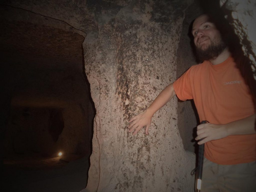 Tony touching a stone pillar in one of Kaymakli's many underground chambers. These rooms are connected by narrow and sloping passages.