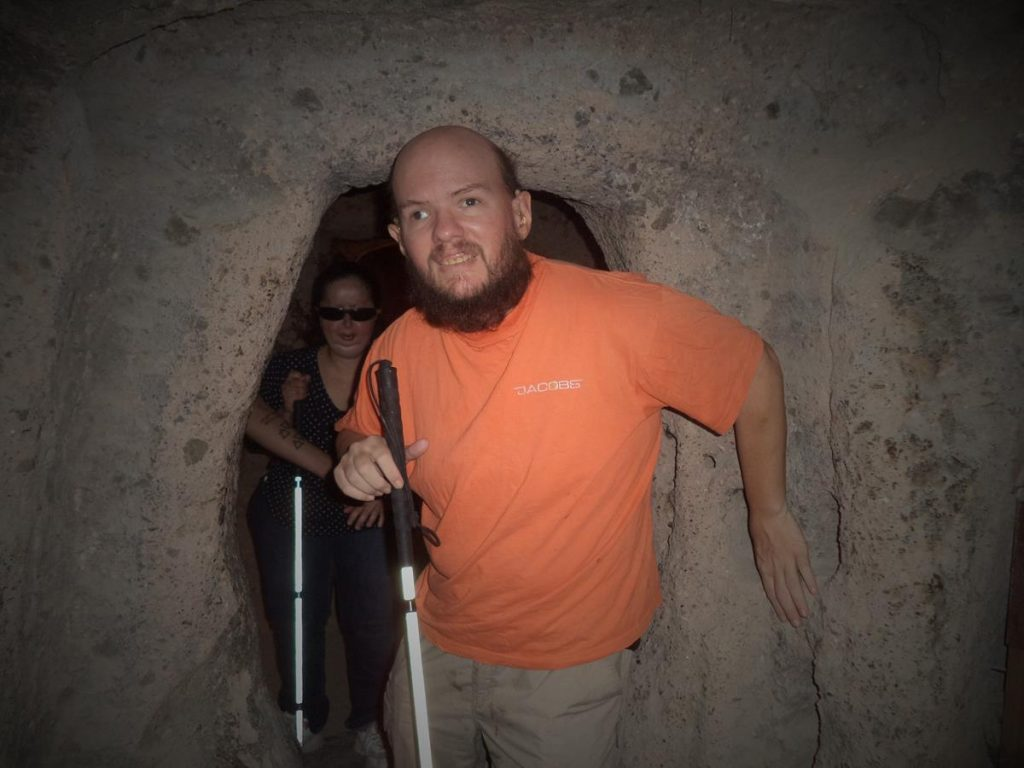 Tony and Tatiana emerging out of a dimly lit rock chamber through a stone doorway.