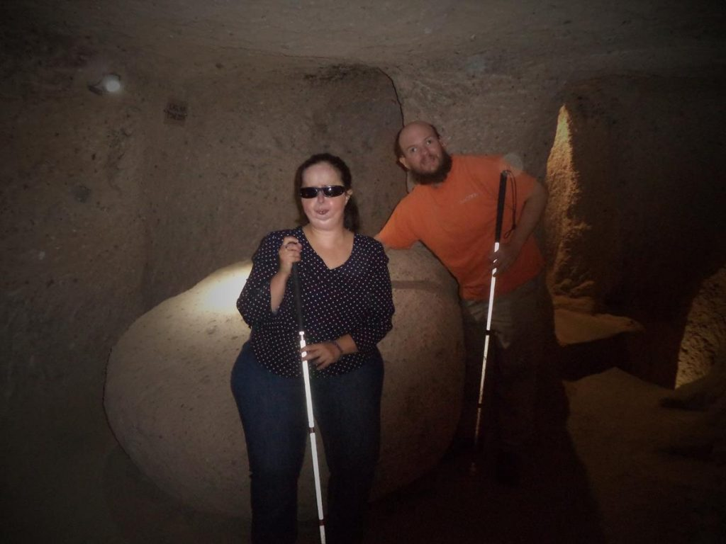 Tatiana and Tony next to a large stone. This is possibly a block of andesite stone, which is located on the underground city's third level. This contains 57 holes which were used for moulding copper ore.