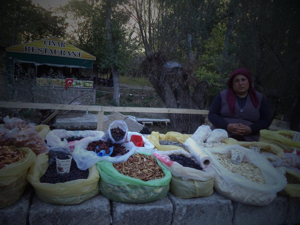 A Turkish woman selling dried fruit, displayed in plastic bags on a wall.