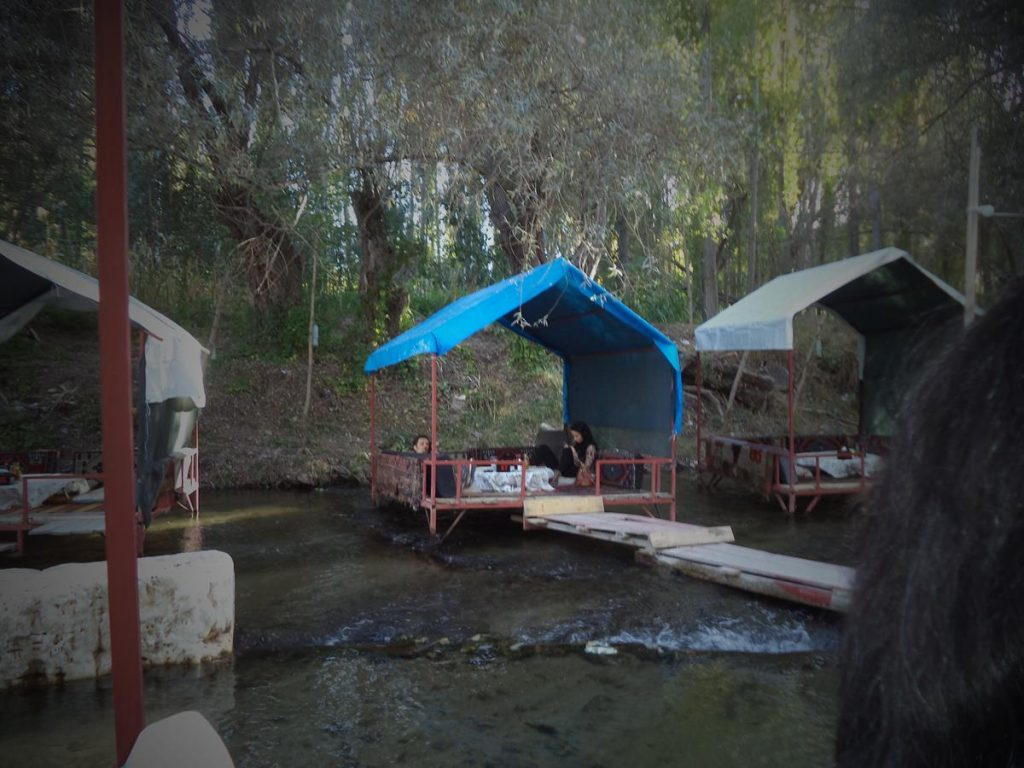 Belisirma restaurant offering a variety of Turkish foods. In view a series of dining tables located on platforms in the middle of Melendiz Stream.