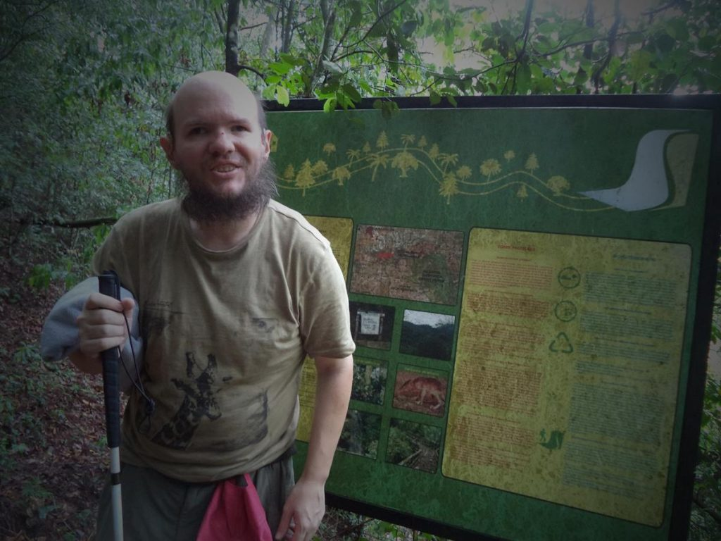Tony next to an information board in the forest.