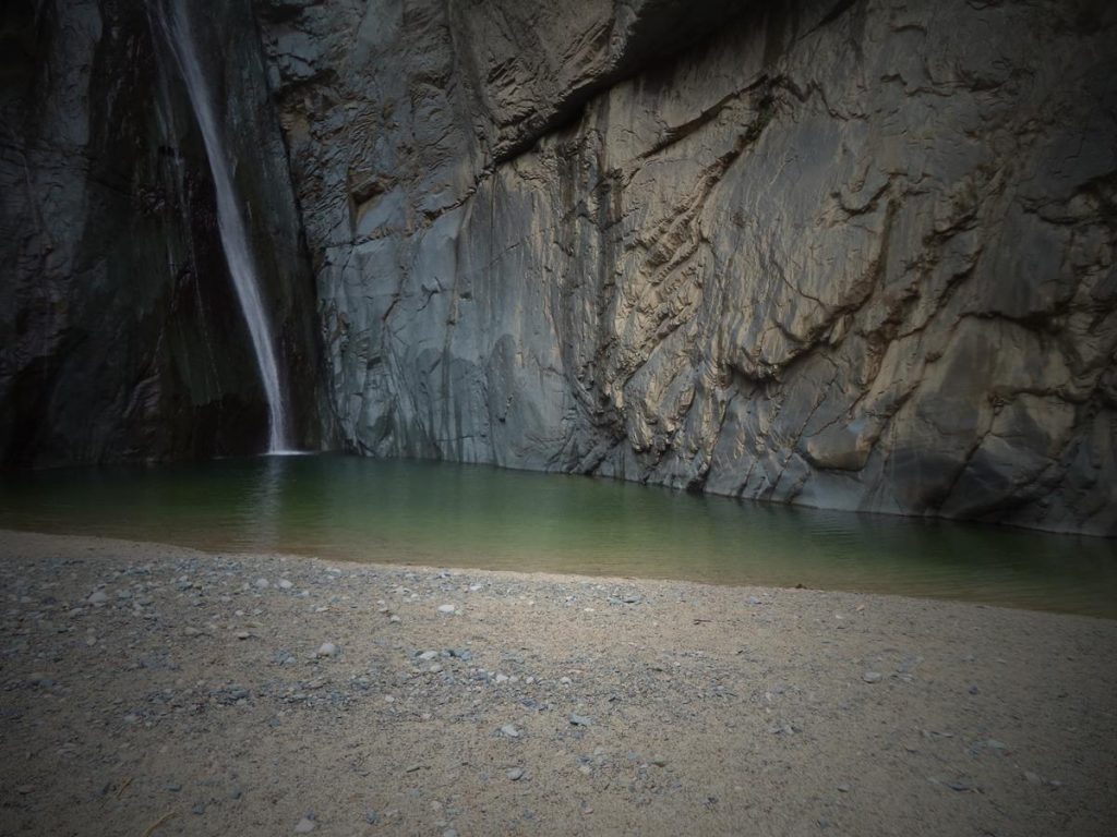 The foot of Jimenoa Falls (Salto Jimenoa). A single narrow stream of water is pouring over a near vertical cliff into a shallow pool. The waterfall looks very calm in this photo, but often the flow of water is much more dramatic. The waterfall is approximately 35 metres in height: only the lower part is in view.