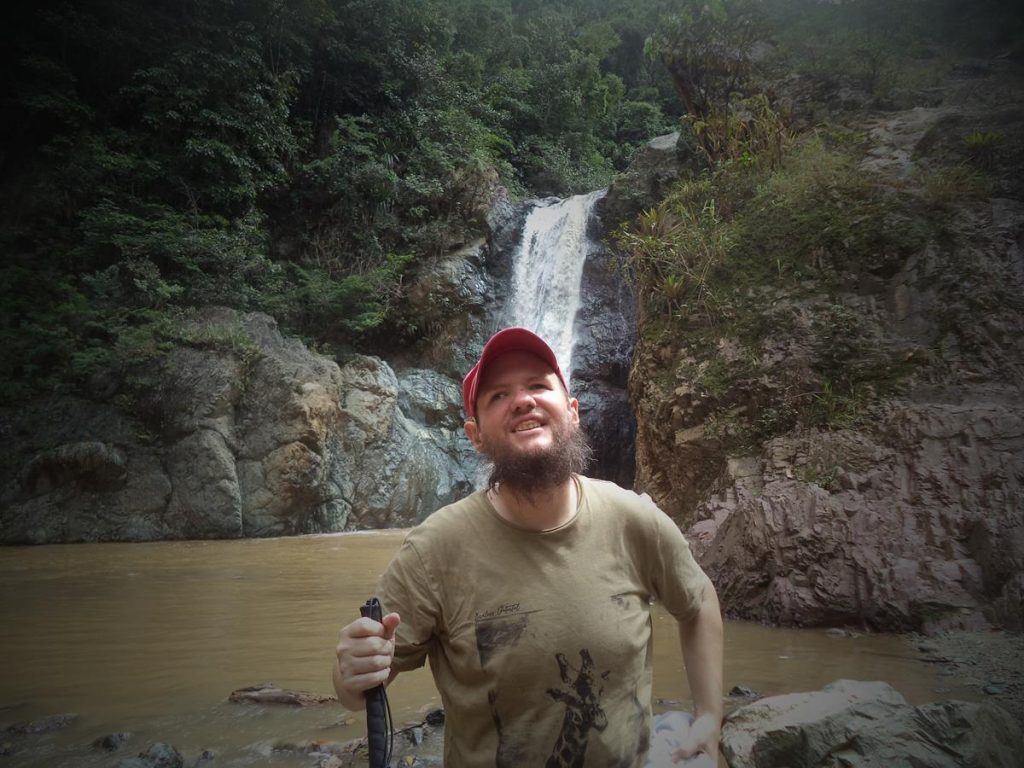 Tony with Baiguate Falls behind. The waterfall is crashing over a cliff into the muddy-looking pool it has created beneath. A steep slope covered in vegetation above.