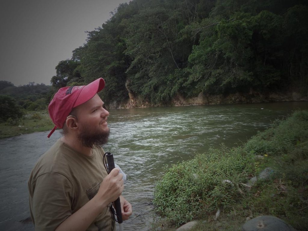 Tony stood by the confluence of the Jimenoa and Yaque del Norte river in Jarabacoa. Forest covering the far bank.