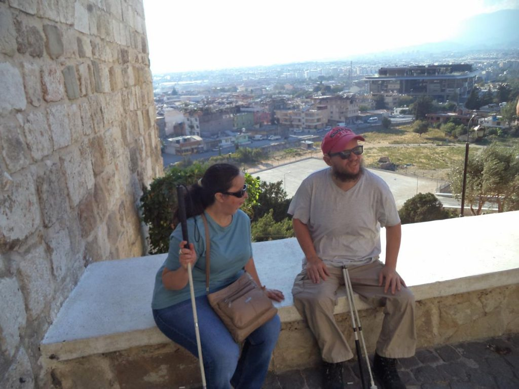 Tony and Tatiana sitting on a low wall with the vista over the city behind.