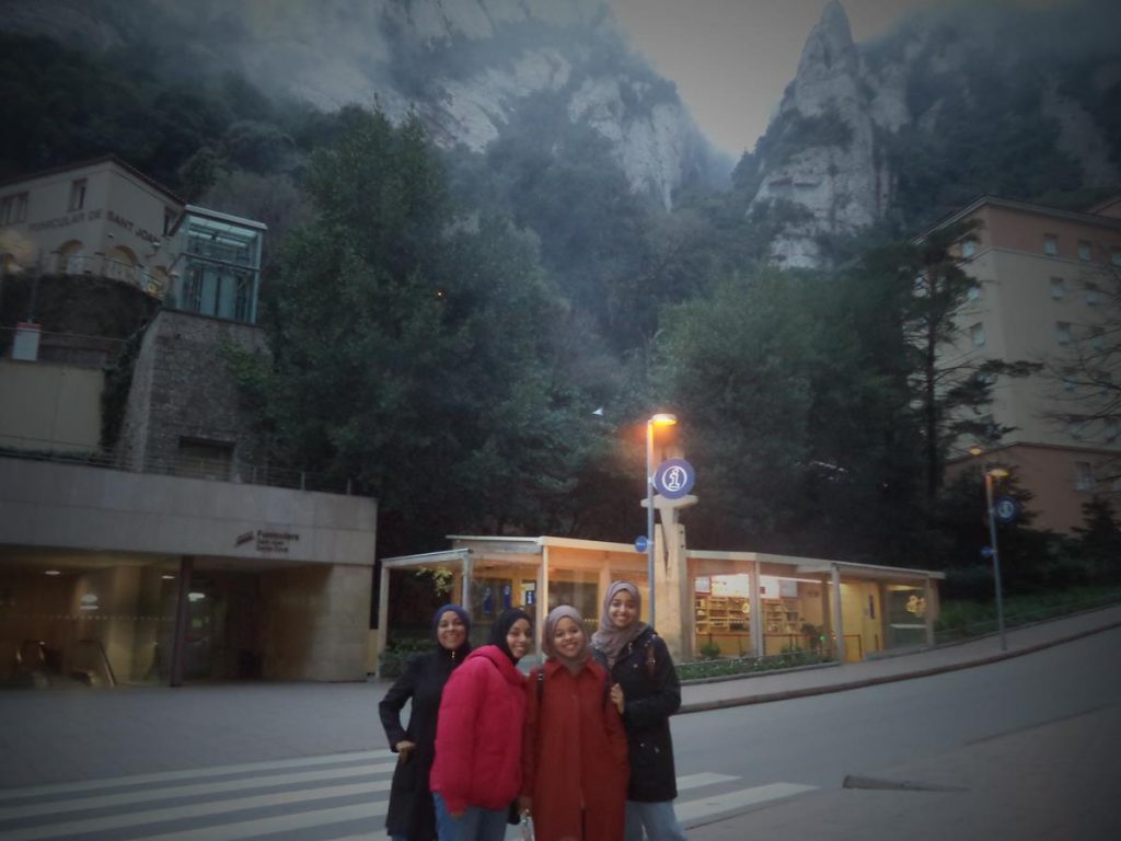 Outside the base of the Sant Joan funicular railway. This travels at gradients of up to 65% to a point higher up the mountain where there are walking trails, sacred sites and view points. A second funicular railway runs down to a shrine at Santa Cova. In the foreground there are four young women wearing head scarfs, possibly of Asian origin.