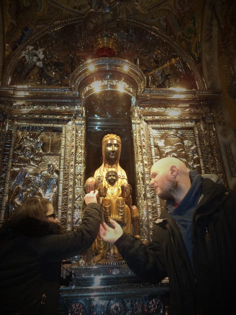 Tatiana and Tony touching the Virgin of Montserrat, a venerated statue of the Madonna and Child, to which the monastery is dedicated. Often referred to as the Black Madonna, she is one of the two patron saints of Catalonia. The statue is approximately 95cm in height with Mary seated on a throne with the Christ Child on her lap. She is holding an orb in her right hand.
