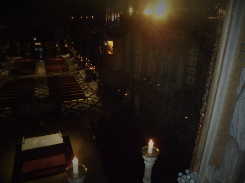 A dimly lit view inside the basilica's nave. Candles in the foreground. Rows of pews below. The nave is 68 metres long and 21.5 metres wide, with a height of 33.3 metres.