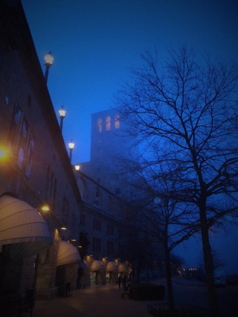 View of the monastery's exterior in semi-darkness and mist. The basilica's bell tower lit up above.