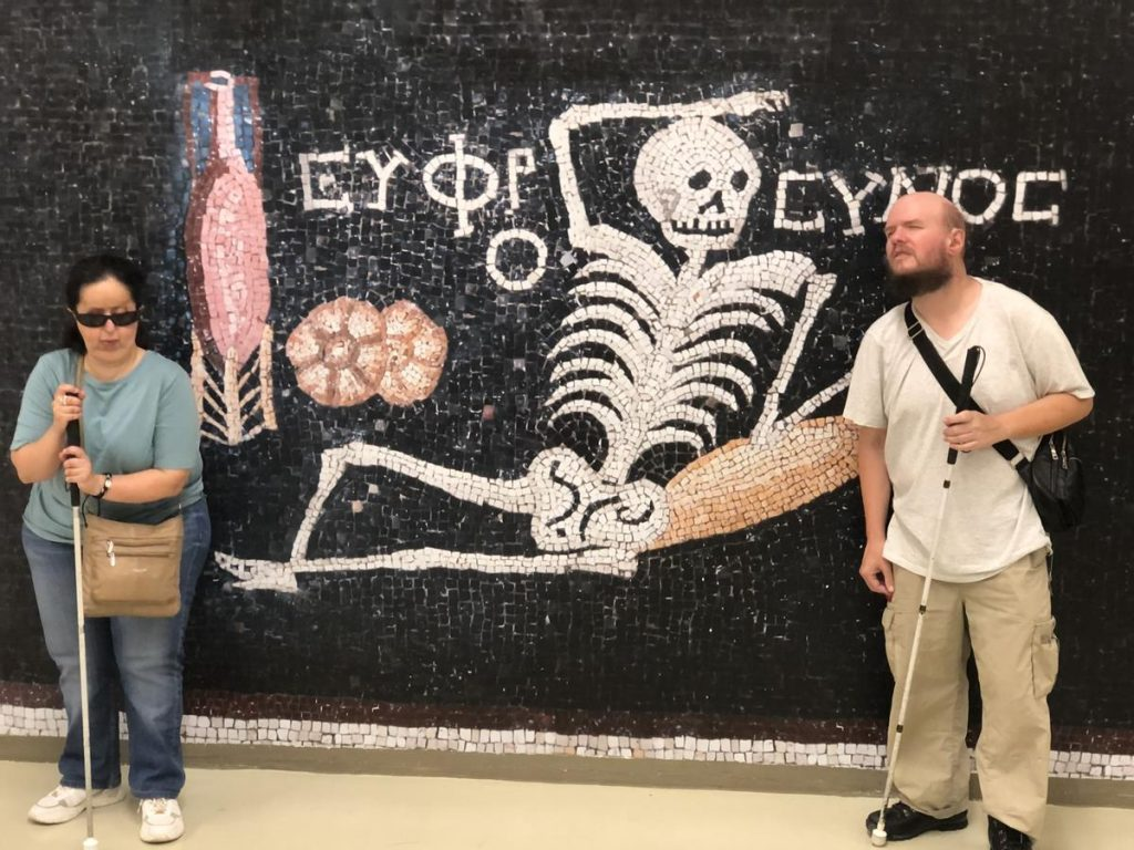 Tatiana and Tony in front of a reproduction of mosaic showing a  reclining skeleton, a pitcher of wine and a loaf of bread. There is an  inscription in Ancient Greek above which has been translated as 'be  cheerful and live your life'.
