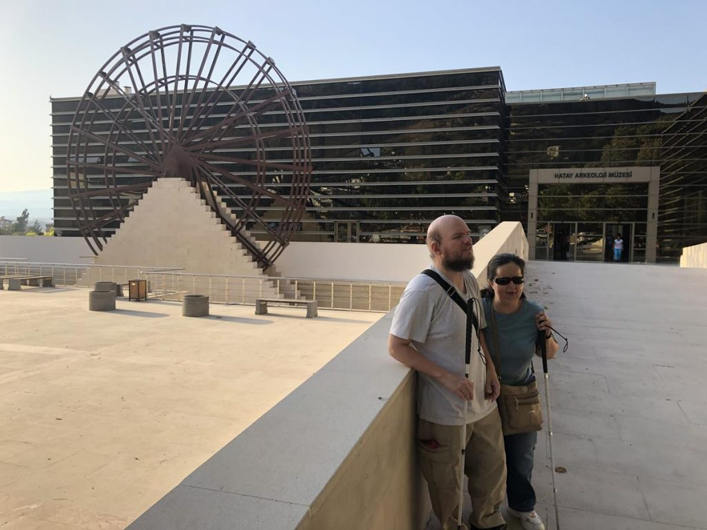 Tatiana and Tony outside Hatay Archaeology Museum. The museum's present building opened in 2014. There is a large decorative metal waterwheel standing in front, which is in the style of waterwheels that historically stood alongside the Orontes River.