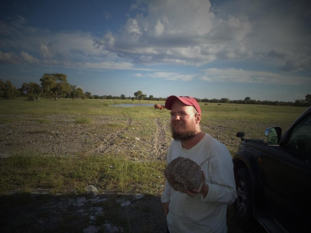 Tony holding a big roughly spherical lump of dry elephant dung.