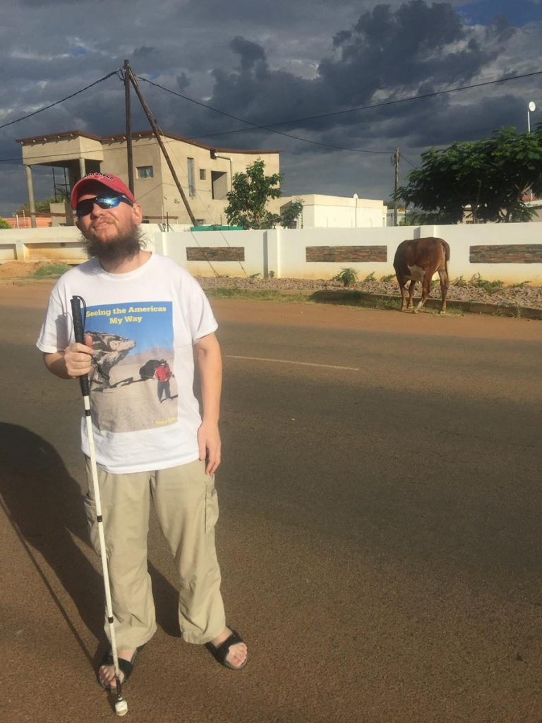 Tony standing in the street, which is located in a suburb of Gaborone called Tlokweng. A cow grazing opposite.