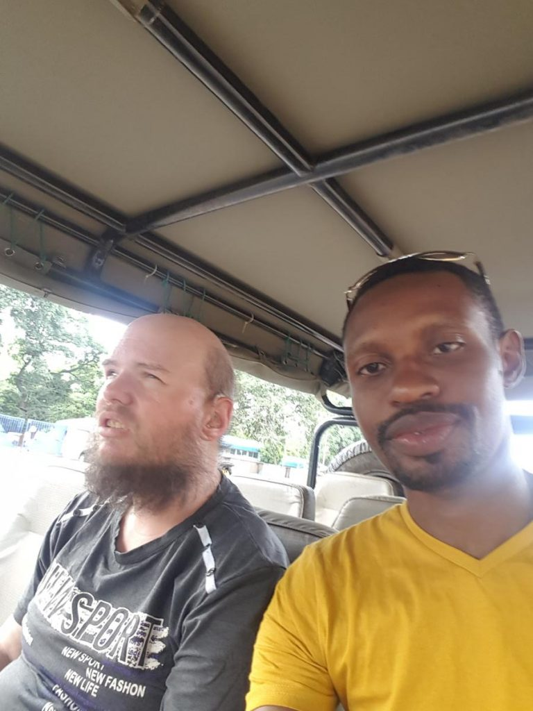 Tony and Ethan sitting in a safari vehicle leaving Livingstone heading to Mosi Oa Tunya National Park.