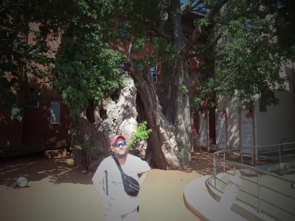 Tony in front of a large three-storey building. A tall tree growing in front. This is the Baobab Prison Tree at the police station in the town of Kasane, north Botswana.
