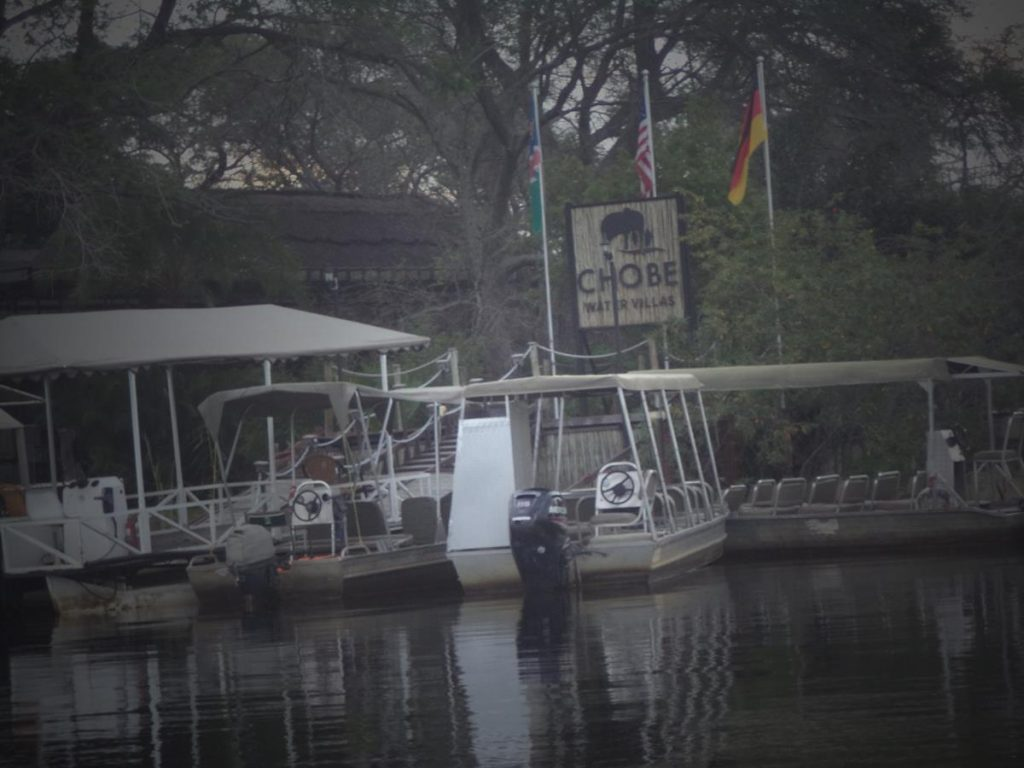 The boat heading into the moorings. Several other boats used for viewing wildlife tied up. Sign for Chobe Water Villas.
