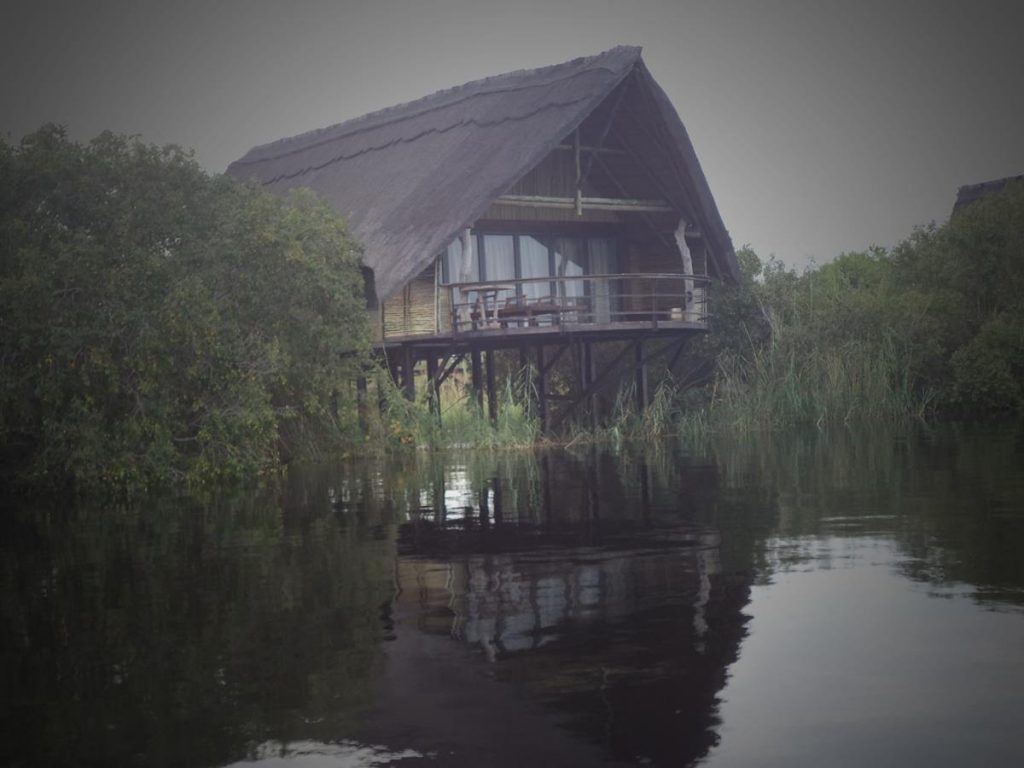 A building at the side of the river. It is raised up on stilts with its roof and walls constructed from reeds.  One of the many tourist villas along the Chobe River.