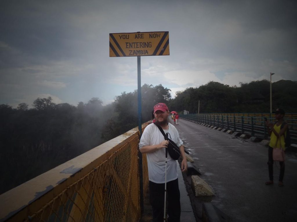 Tony on Victoria Falls Bridge in front of a sign that reads 'You are now entering Zambia'. The bridge is 198 metres long, with its main steel arch spanning 156 metres. It is elevated 128 metres above the Zambezi River.