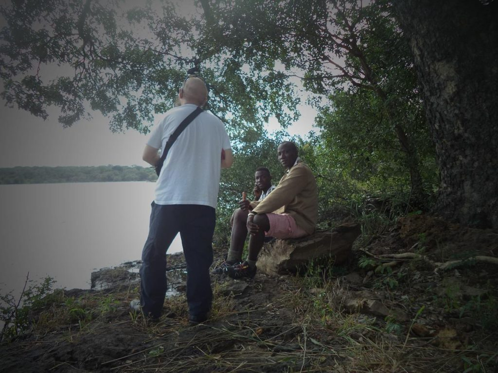 Tony with the two local guys next to the Zambezi. Tony facing away from the camera.